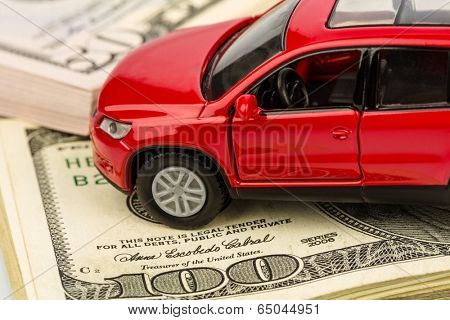 a car stands on dollar banknotes. cost of buying a car, fuel, insurance and other car costs