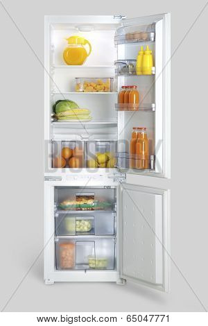 open refrigerator and freezer stocked with fruits, vegetables, drinks