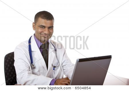 Feliz el hombre médico está trabajando en el ordenador portátil en su oficina