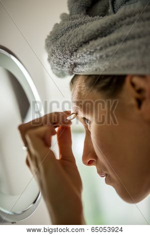 Woman Plucking Her Eyebrows In The Mirror