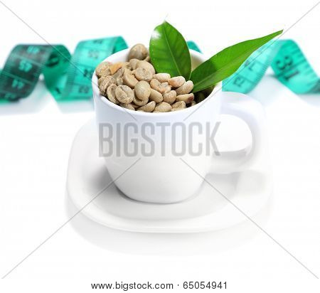 Raw green coffee beans in cup and measuring tape, isolated on white. Concept of weight loss