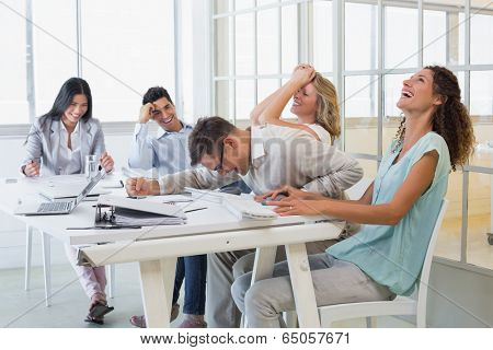 Casual business team laughing during meeting in the office