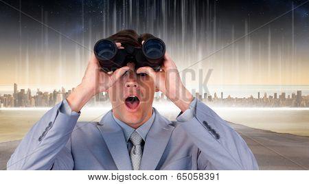 Suprised businessman looking through binoculars against cityscape on the horizon