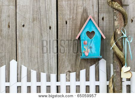 Teal blue birdhouse hanging over white picket fence next to vine wrapped honey locust tree