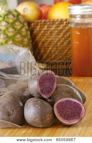 Fresh blue potatoes in plastic sack in kitchen