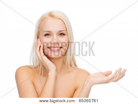 health, cosmetics, advertising and beauty concept - smiling woman holding imaginary lotion jar and applying it