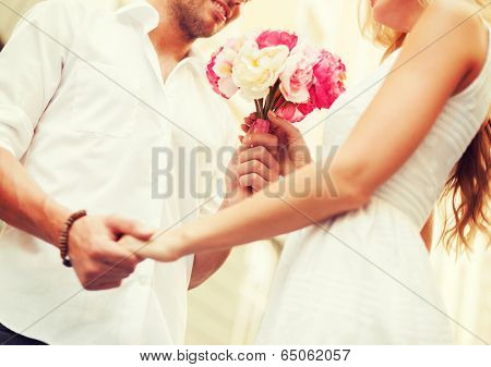 summer holidays, love, relationship and dating concept - couple with bouquet of flowers in the city