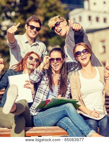 summer holidays, education, campus and teenage concept - group of students or teenagers with books, notebooks, files and folders