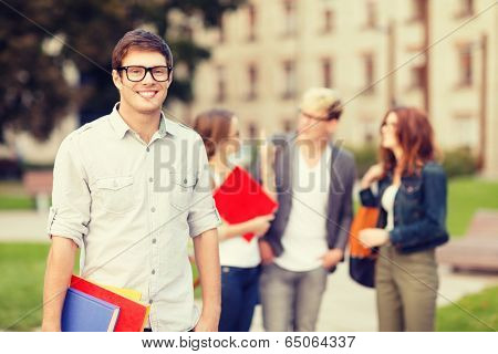 summer holidays, education, campus and teenage concept - smiling teenage boy in eyeglasses with classmates on the back