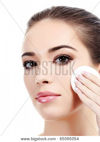 Beautiful woman using a cotton pad to remove her makeup. Isolated on white background, copyspace