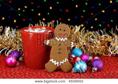 Cocoa And A Gingerbread Cookie In Night Setting With Christmas Lights.