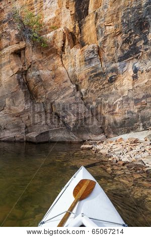 canoe bow with a paddle on Horsetooth Reservoir with a high sandstone cliff, Fort Collins, Colorado