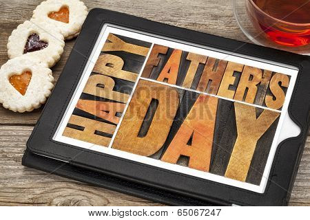 happy father's day - a word abstract in antique wood letterpress printing blocks on a digital tablet with heart biscuit cookies