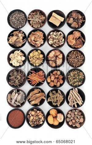 Large chinese herbal medicine selection in wooden bowls over white background.