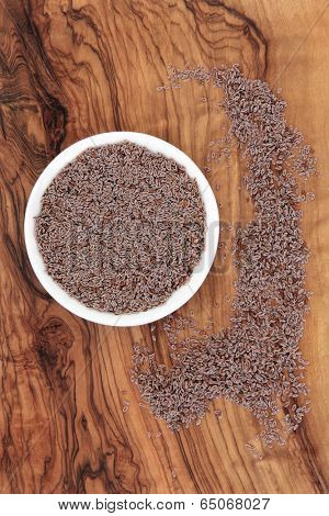 Psyllium seed in a white porcelain bowl on an olive wood background. Ispaghula. Cholesterol reducing and laxative..