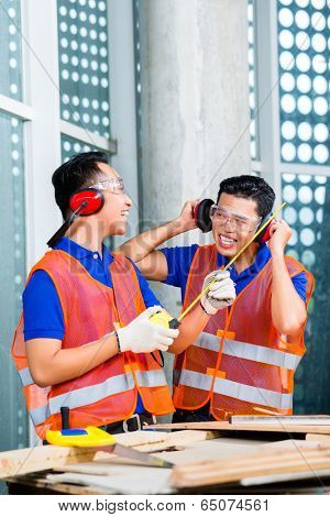 Asian Indonesian builder or craftsman and supervisor with ear or hearing protection and glasses on a tower building or construction site