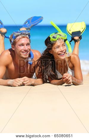 Beach couple having fun snorkeling on vacation. Happy young multiracial couple lying on summer beach sand with snorkel equipment after swimming with fins and mask on travel holidays.