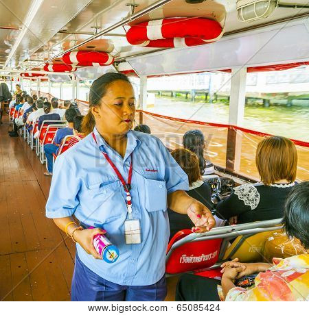 Lady In A Boat Sells Tickets For Public Transportation At The Ferry In Bangkok