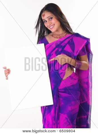 girl in pink sari holding white board