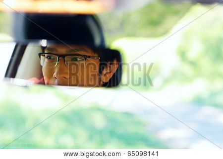 Portrait of a happy asian man sits on driver's seat and Looks in the rear-view mirror