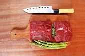 picture of veal  - red fresh raw beef veal fillet with asparagus and stainless steel chef knife on cutting plate over wooden table prepared to use - JPG