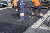 image of tar  - Workers on Asphalting paver machine during Road street repairing works - JPG