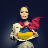 stock photo of democracy  - Young woman opening shirt painted in colors of ukrainian flag like superhero - JPG