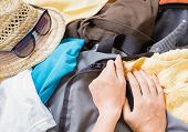 foto of zipper  - Woman trying to fasten the zipper on travel bag - JPG