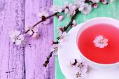 stock photo of crockery  - Fragrant tea with flowering branches on wooden table close - JPG