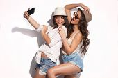 pic of young woman posing the camera  - two young women taking selfie with mobile phone - JPG