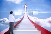 foto of goal setting  - The word goal setting and businessman holding glasses against red steps arrow pointing up against sky - JPG