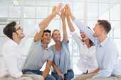 stock photo of 5s  - Group therapy in session sitting in a circle high fiving in a bright room - JPG