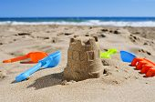 pic of shovel  - a sandcastle and toy shovels on the sand of a beach - JPG