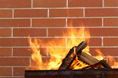 picture of brazier  - burning wood in a brazier on the brick wall background