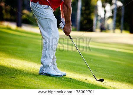 Male golfer shooting a golf ball from green grass