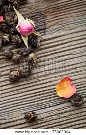 Fresh green tea leaves with rose buds
