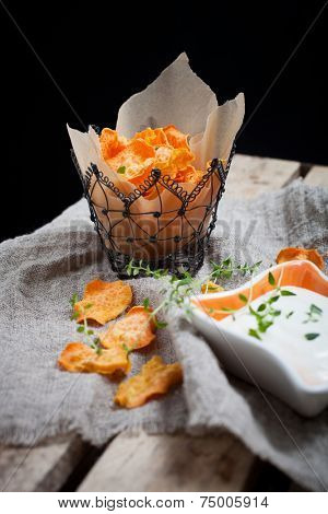 Homemade sweet potato chips with fresh thyme