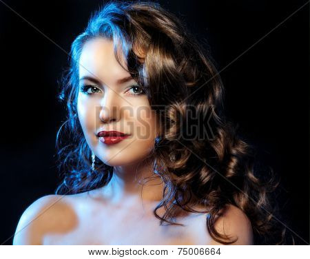 beautiful young woman with long curly hair against dark studio background