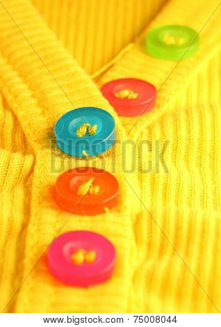 Colorful resin buttons on a yellow shirt.