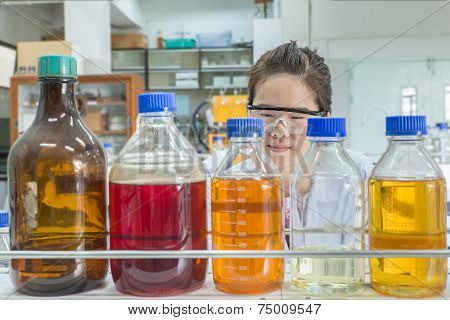 Close Up Of Beautiful Asian Scientist Looking At Chemical Bottle