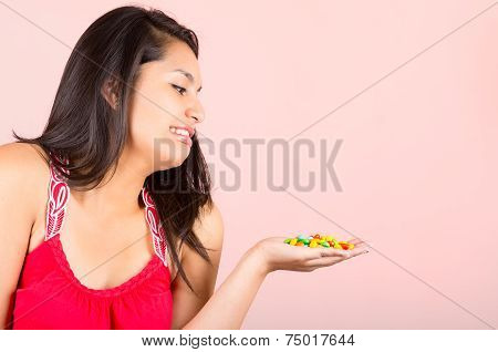 Pretty young teenage girl student looking at candy sweets