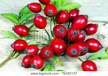 Several Rosehips With Leaves On A Wooden Table