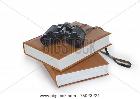 field-glass and heap of books, tool for information search.