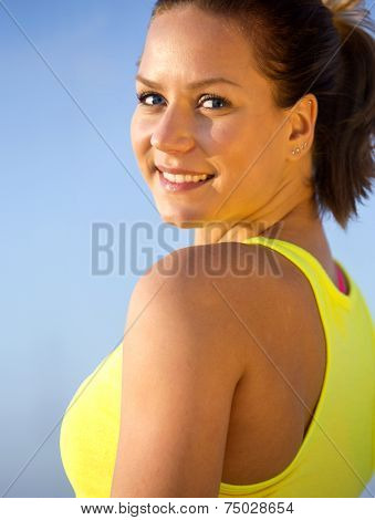 Portrait, of a fit, spontaneous ane athletic woman, looking brightly and smiling over her shoulder, on a warm summer evening