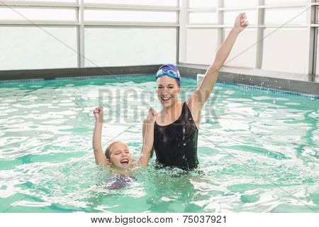 Cute little girl learning to swim with coach at the leisure center