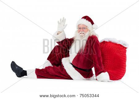 Santa sits leaned on his bag and waves on white background