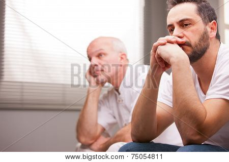 Men Concerned About Something In A Living Room