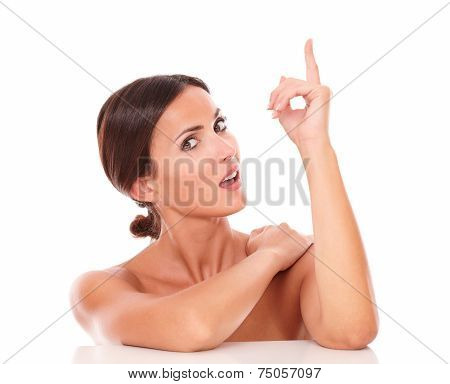 Latin Woman Pointing Up And Looking At Camera