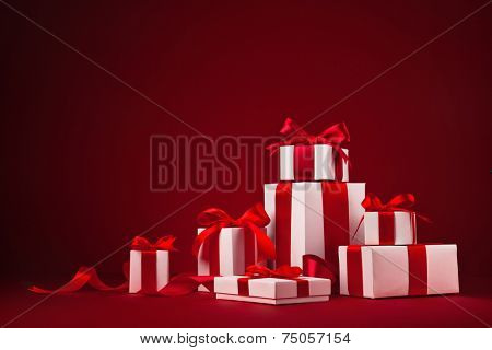 Christmas gifts with red bows and ribbons on red background
