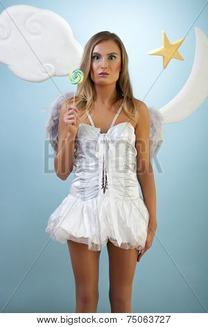 Girl in white angel costume looks like a doll in front of a fairytale background with a lollipop in her hand.